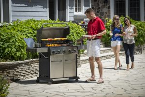 Broil King Baron S 590 Pro Liefestyle Image with man at barbecue and two female friends walking arm in arm towards barbecue