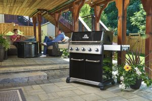 Broil King Baron 520 Pro Lifestyle IMage - Patio with 2 guys sitting near barbecye