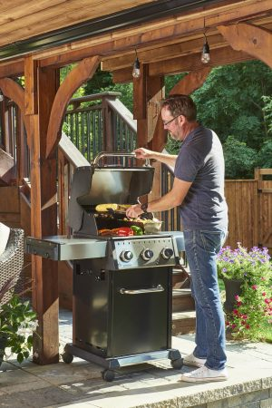 Broil King Baron S 320 Lifestyle - Man cooking on the grill