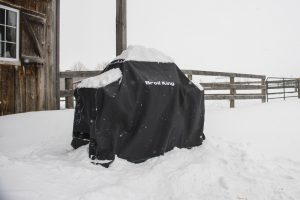 Broil King Premium Grill Cover 68491 on a Broil King barbecue outside and protecting the barbecue from a recent snow fall